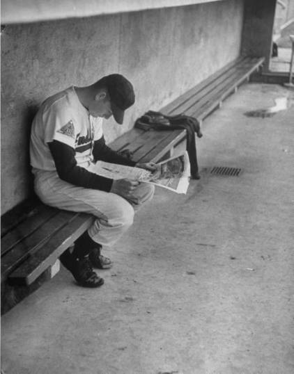 Baseball player Billy Joe Davidson sitting alone in the dugout reading a newspaper before a game.jpg